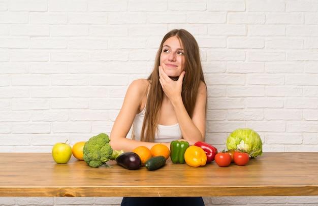 アイデアを考えて多くの野菜を持つ若い女