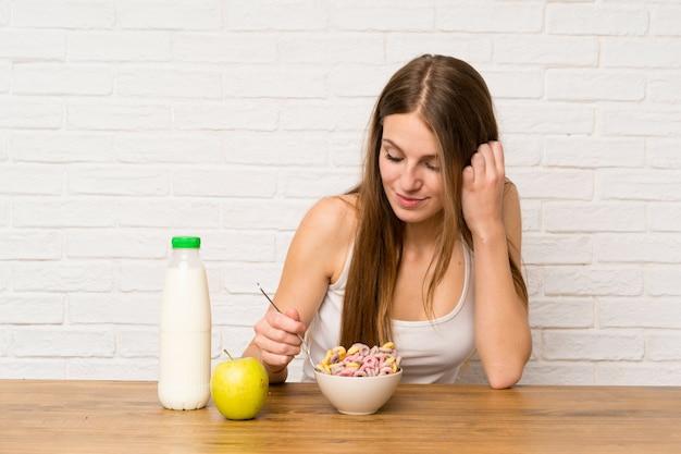 Молодая женщина завтракает с миской каш