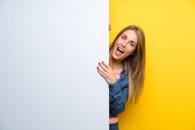 Молодая женщина держит пустой плакат, делая жест сюрприз