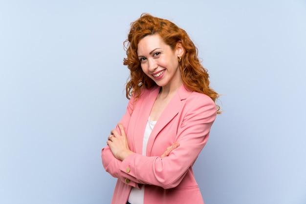 腕を組んで、楽しみにして分離の青い壁の上のスーツの赤毛の女性