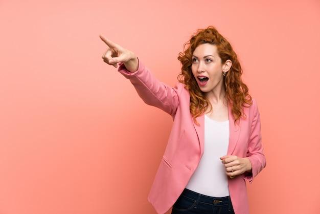離れて指している孤立したピンクの壁の上のスーツの赤毛の女性