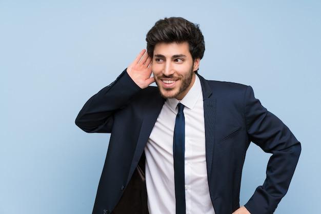 耳に手を置くことによって何かを聞いて孤立した青い壁上のビジネスマン