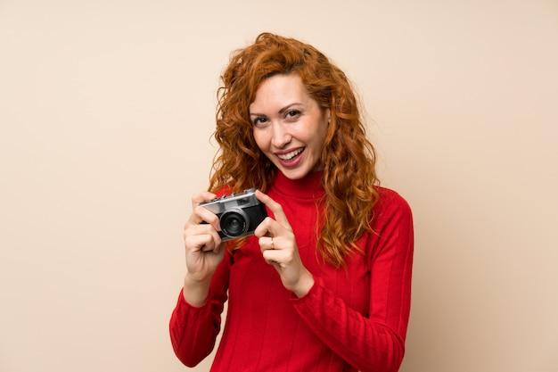 カメラを持ってタートルネックセーターと赤毛の女性