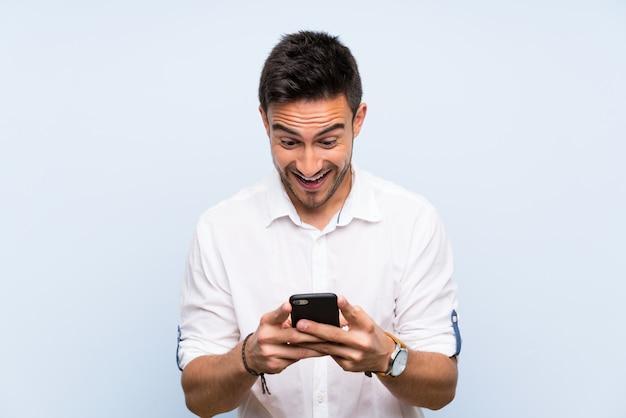 孤立した青い上ハンサムな若い男は驚いて、メッセージを送信する