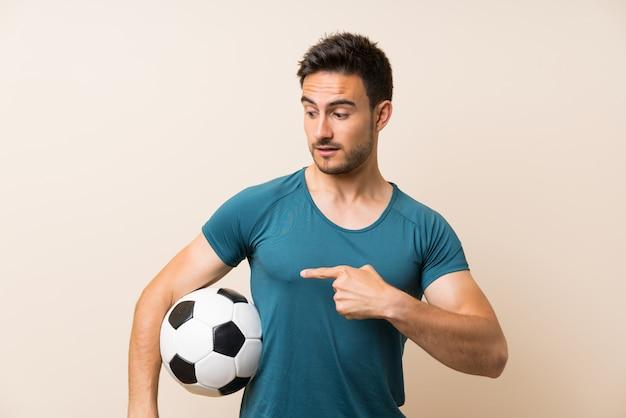 サッカーボールを保持している分離の上ハンサムなスポーツ男