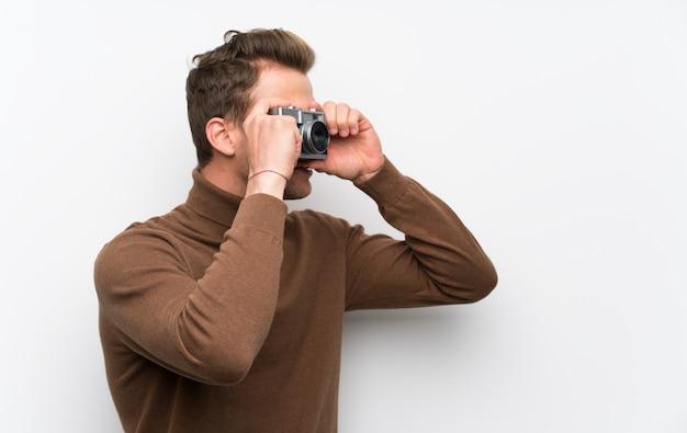 カメラを持って孤立した白い壁に金髪の男