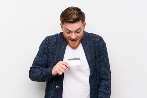 赤毛の男がクレジットカードを保持