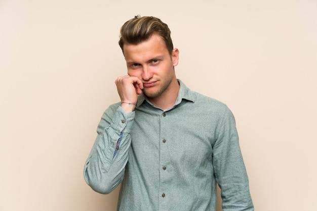 不幸な欲求不満と孤立した壁の上の金髪のハンサムな男