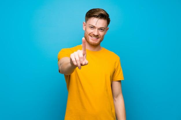 表示と指を持ち上げる青い壁の上の赤毛の男