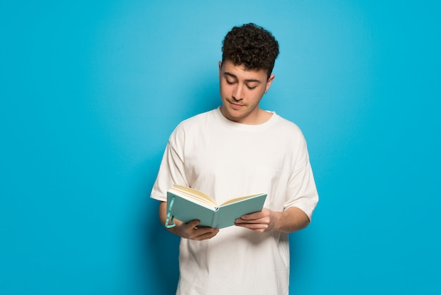 本を持っていると読書を楽しんでいる青の上の若い男