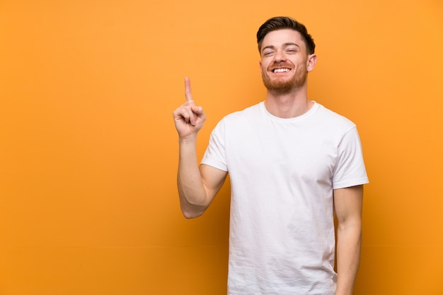 茶色の壁を見せて、最高のサインで指を持ち上げる赤毛の男