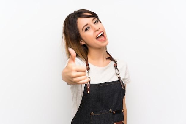 Молодая женщина с фартуком с пальцами вверх, потому что случилось что-то хорошее