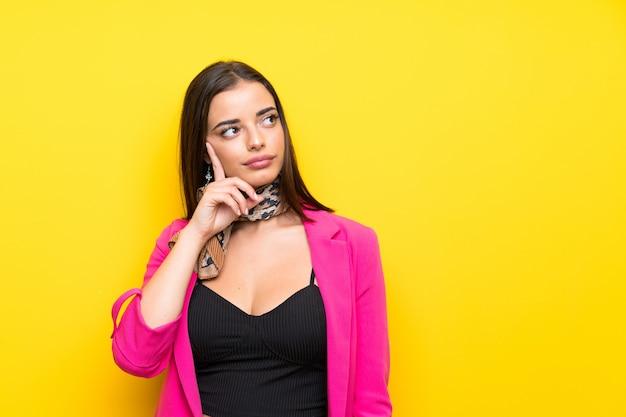 Молодая женщина над изолированным желтым думая идея