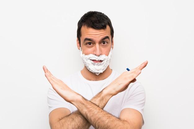 Человек брить бороду над изолированной белой, не делая жест