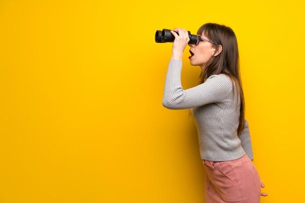 黄色の壁を越えて、双眼鏡で遠くを見ている眼鏡の女