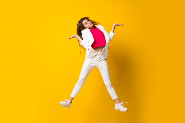 疑問を持つ孤立した黄色の壁を飛び越えて若い女性
