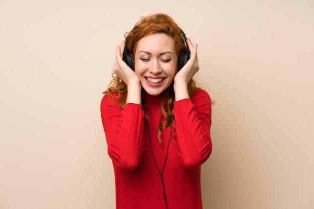 ヘッドフォンで音楽を聴くのタートルネックセーターと赤毛の女性