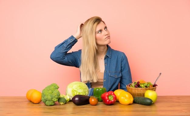 頭を掻きながら疑問を持つ多くの野菜を持つ若いブロンドの女性