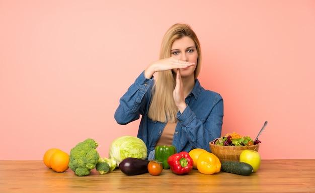Молодая белокурая женщина при много овощей делая жест перерыва