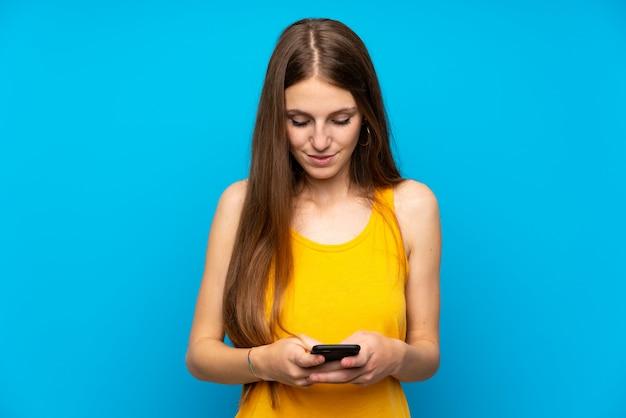 携帯電話でメッセージを送信する孤立した青い壁の上の長い髪を持つ若い女