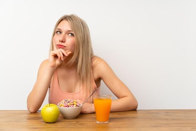 Молодая белокурая женщина имея завтрак думая идея
