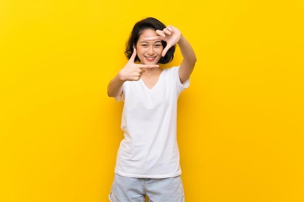 顔を集中して孤立した黄色の壁を越えてアジアの若い女性。フレーミングシンボル