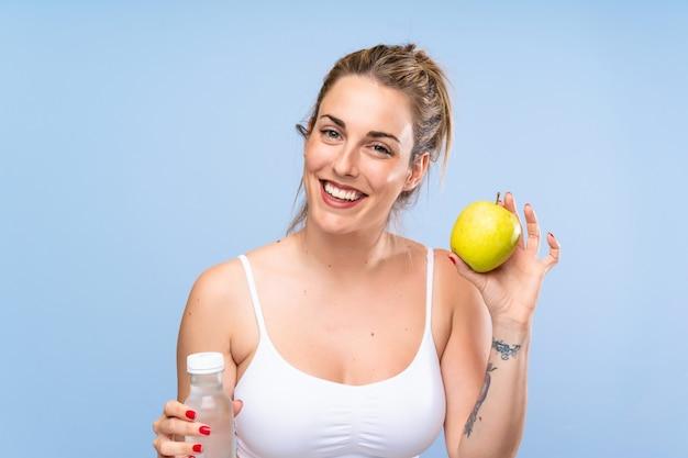 リンゴと水のボトルを持つ幸せな若いブロンドの女性