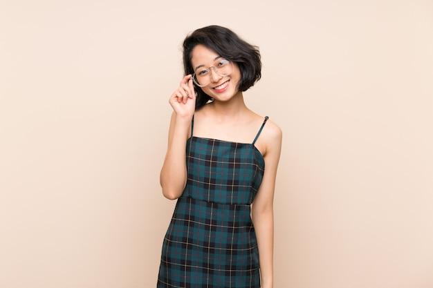 メガネと幸せと孤立した黄色の壁を越えてアジアの若い女性