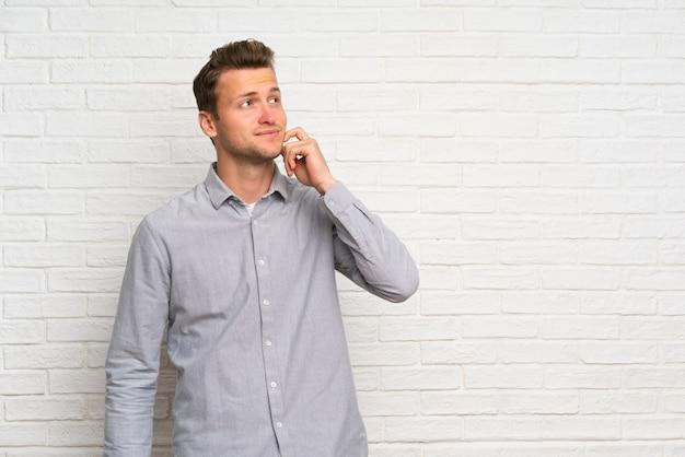 Белокурый человек над белой кирпичной стеной думая идея пока смотрящ вверх
