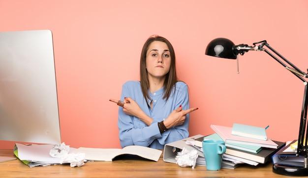 Молодая девушка студент, указывая на боковые стороны, имеющие сомнения