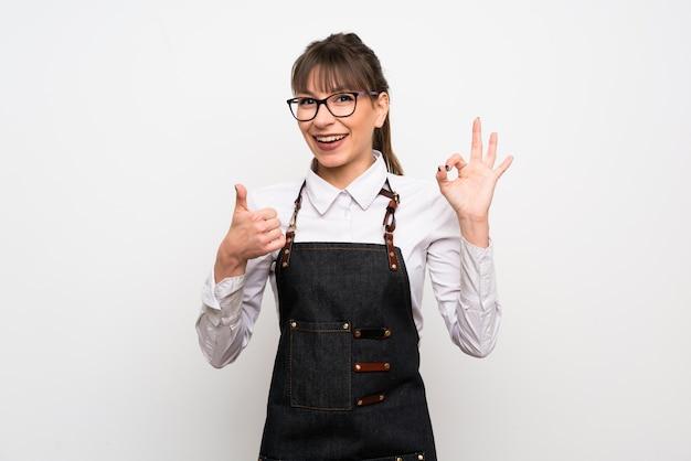 Молодая женщина с фартук, показывая знак ок и большой палец вверх жест