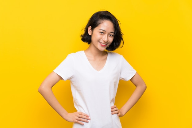 アジアの若い女性の分離の黄色い壁の上の腕でポーズをとってポーズと笑顔