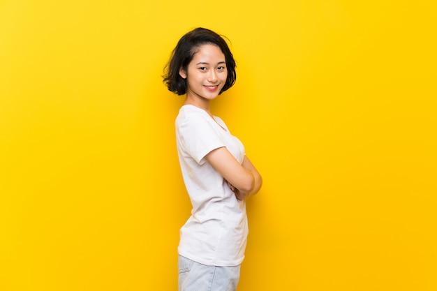 腕を組んで、楽しみにして分離の黄色の壁の上のアジアの若い女性