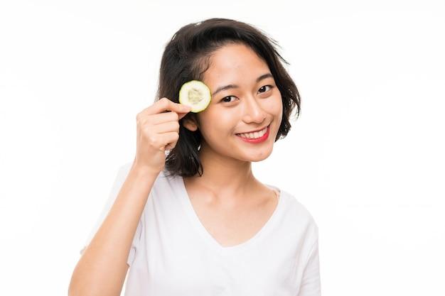 Азиатская молодая женщина над изолированными держа ломтиками огурца