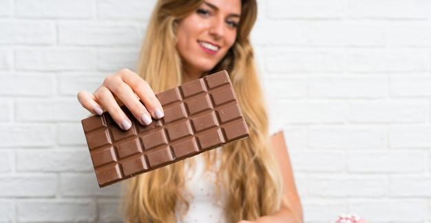 チョコレートを持つ若いブロンドの女性