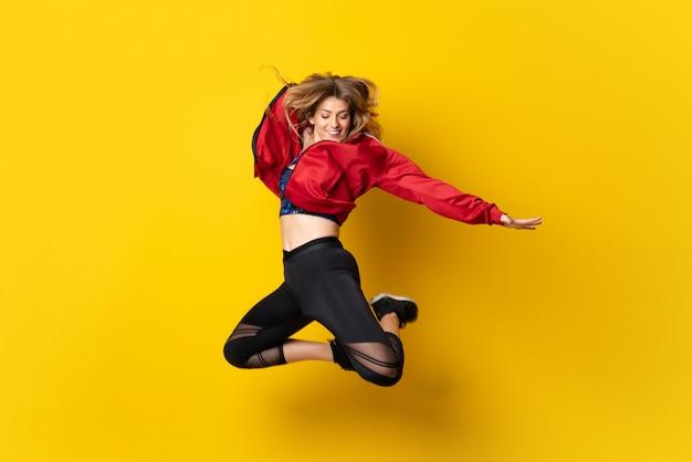 孤立した黄色の上で踊ってジャンプと都市のバレリーナ