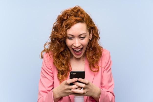 孤立した青い壁にスーツを着た赤毛の女性が驚いてメッセージを送信