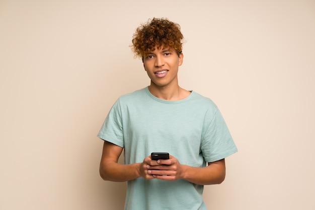 携帯電話でメッセージを送信する緑のシャツを持つアフリカ系アメリカ人
