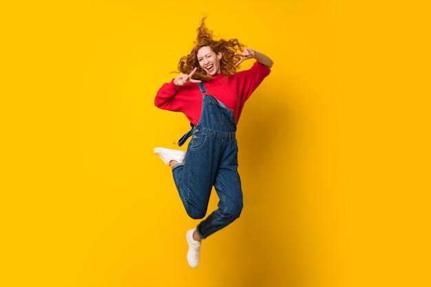 分離の黄色の壁を飛び越えてオーバーオールを持つ赤毛の女性