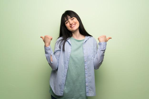 両手で親指ジェスチャーを与えると笑顔の緑の壁を越えて若い女性