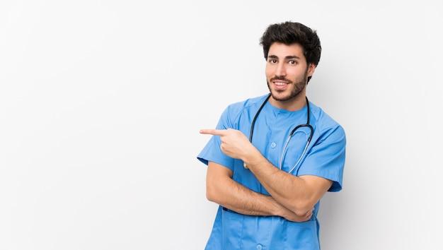 側に指を指している孤立した白い壁の上の外科医医師男