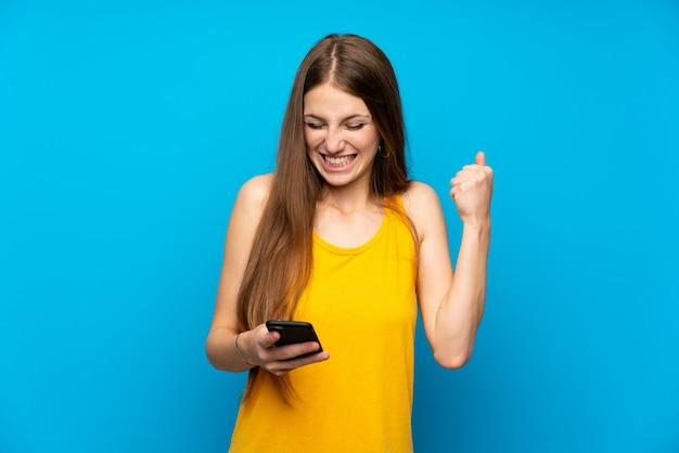 勝利の位置で携帯電話で孤立した青い壁を越えて長い髪を持つ若い女