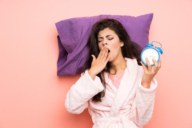 Девушка-подросток в халате на розовом фоне держит винтажные часы