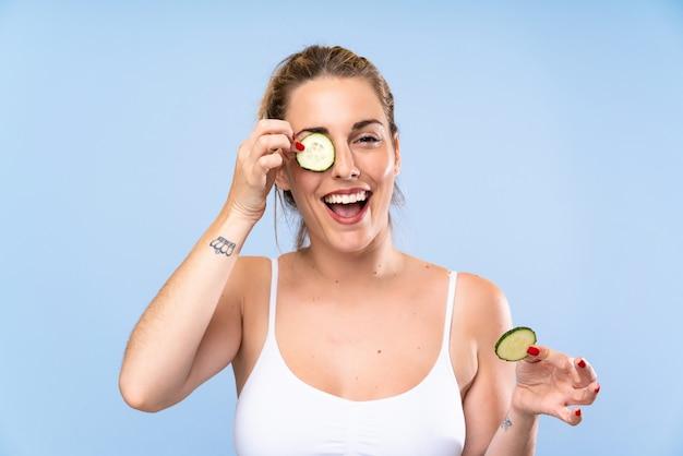 Счастливый красивая молодая женщина, держащая ломтики огурца