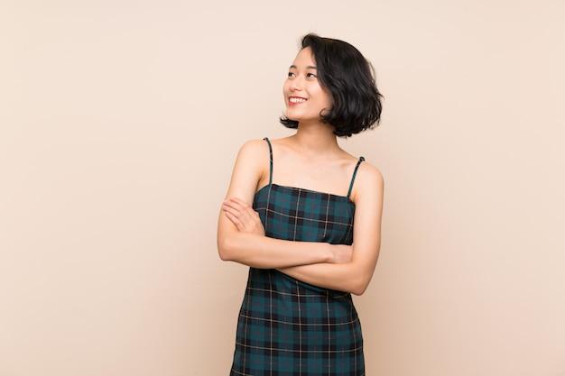 幸せと笑顔の孤立した黄色の壁の上のアジアの若い女性