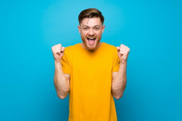 勝者の位置で勝利を祝っている青い壁の上の赤毛の男