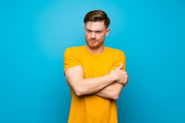動揺を感じて青い壁の上の赤毛の男