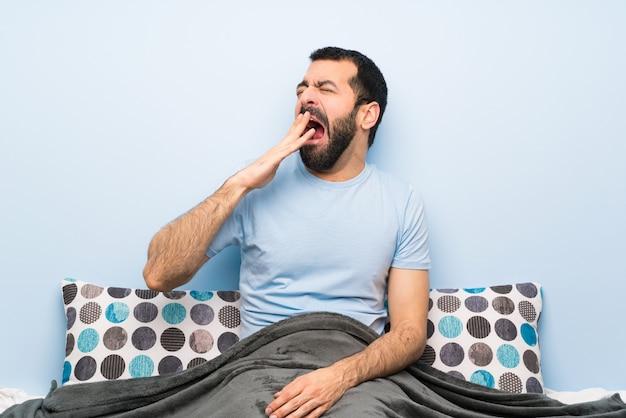 あくびと手で広い口を覆っているベッドの男