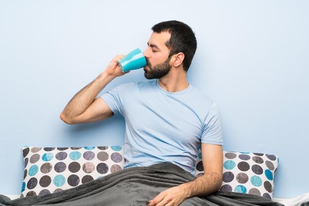 一杯のコーヒーを保持しているひげとベッドの中で男