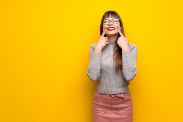 幸せで快適な表情を浮かべて黄色の壁の上の眼鏡を掛けた女性